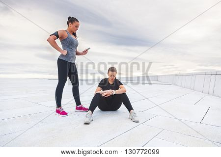 Two women checking workout statistics on their electonic devices. They are wearing gray and black sportswear and resting after fitness exercises. Technology and health lifestyle concepts