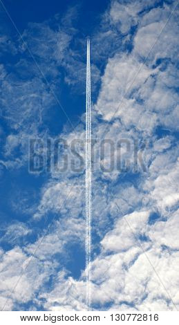 Jet plane contrail against white clouds in a blue sky