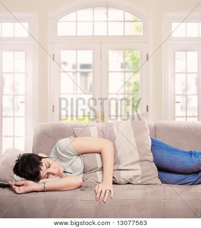 Young woman sleeps on the couch in the livingroom.