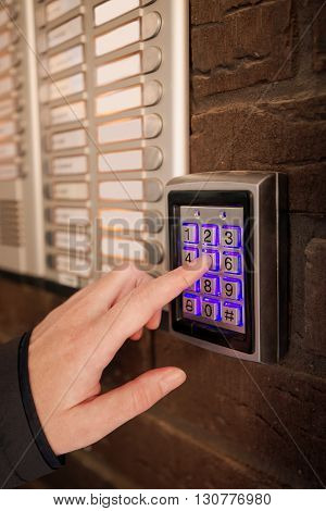 Woman dialing passcode on security keypad intercom to open entrance door of the apartment building.