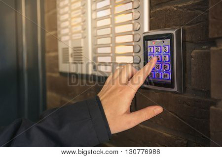 Woman dialing pass code on intercom security keypad to open entrance door of the apartment building. poster