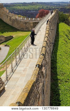 LINCOLN ENGLAND - MAY 3: Middle-aged man and woman take a selfie photo using camera on end of selfie stick on the walls of Lincoln Castle. Lincoln England. On 3rd May 2016.