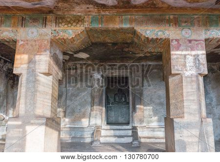 Chettinad India - October 15 2013: Shot from entrance of Chithannavasal Cave Temple into the alcove-like inner sanctum showing the Jain idol. Strong thick pillars and faded paint on the ceiling and walls.