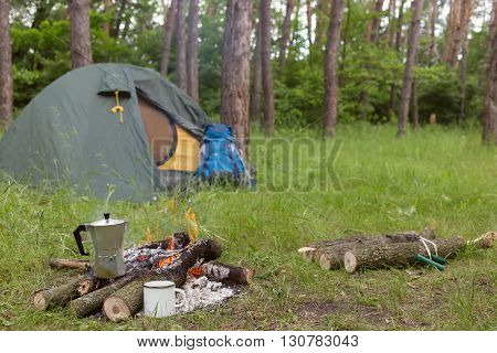 Camping in the woods with a fire in a clearing.