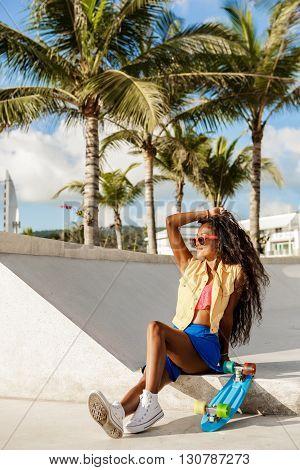 Beautiful Teenage Black Girl In Blue Skirt Sit With Her Penny Longboard.