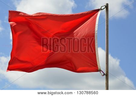 Red warning flag on the beach background