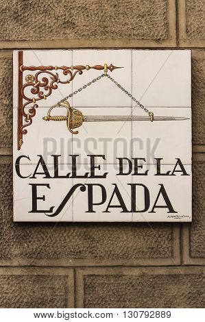 MADRID, SPAIN - MARCH 13, 2016: Closeup of the street sign. Street signs in Madrid are hand-painted ceramic tiles typically composed within 9 or 12 tiles. They depict the name of the alley or street as well as illustrations that indicate special meanings.