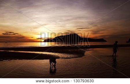 Two boys playing in a beach at sunset.