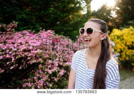 Girl in sunglasses laughs merrily. Behind her, the lush flowering shrubs and green trees