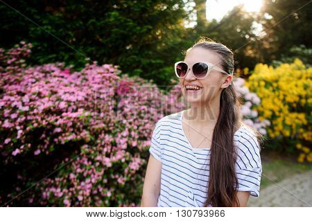 Dark-haired young woman in large sunglasses standing on the background of the picturesque park. She laughs merrily