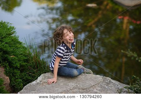 The boy with blond tousled hair sitting on a big gray stone. Behind him, a pond surrounded by green trees and bushes