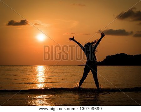 silhouette of happy young woman jumping in sea at sunset beach in summer. Freedom life concept. Holiday. vacation.