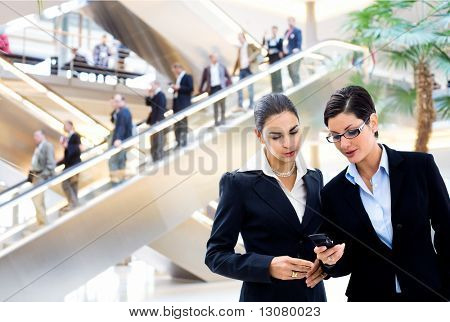 Two young businesswomen sharing text message on mobile phone in lobby, with businessmen traveling on escalator in background.