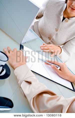 Businesswomen doing paperwork at office, close-up on hands and papers.