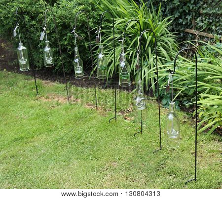 A Collection of Hanging Glass Bottle Candle Holders.