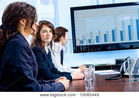 Team of happy young businesspeople having meeting in boardroom at office in front of a huge plasma TV screen, indoor, smiling.