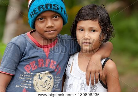 BUKIT LAWANG, INDONESIA, JULY 12, 2010 : Little brother and sister are posing outside near the Bukit Lawang village, Sumatra, Indonesia