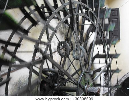 The rotary motion of the water wheel in an old historic watermill in italian village . Borghetto fraction of Valeggio sul Mincio (province of Verona) Italy