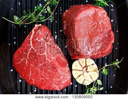 Fresh close up Raw Beef Filet steak with thyme, garlic, salt on grilled pan
