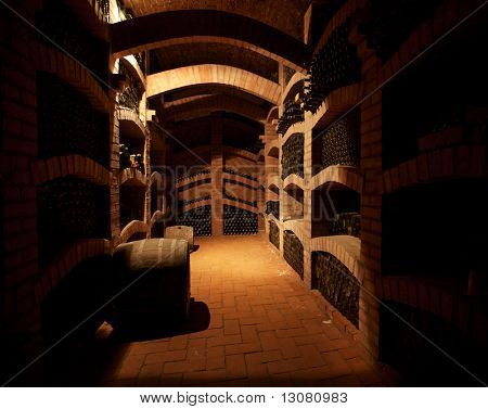 Winebottles stacked in the old cellar of the winery.