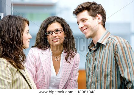 Happy young business people talking in front of office window, smiling, friendship.