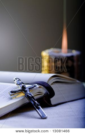 Old Cross and the Holy Bible laying on the table in front of a lighting candle.