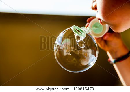 Achlid blowing a soap bobble in summer time