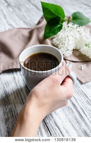 Coffee cup in a female hand on a wooden table