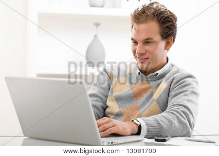 Young man working on laptop computer at home.