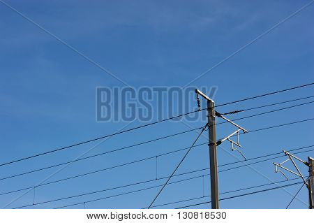 Railway power line supports and wires on a clear blue sky background