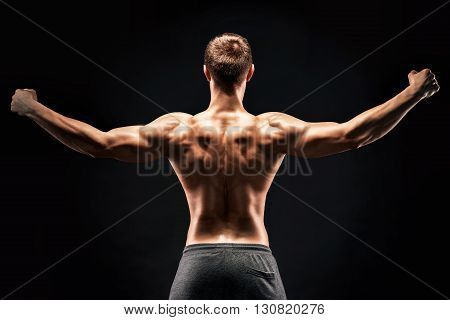 Rear view of healthy muscular young man showing back, perfect shoulders, biceps, triceps on black background.