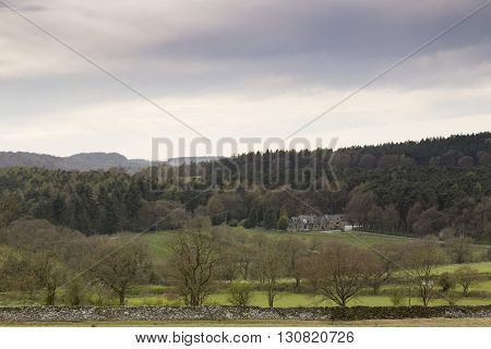 An image of a magnificent home surrounded by trees in the beautiful countryside shot from Bradgate park Leicestershire England UK.
