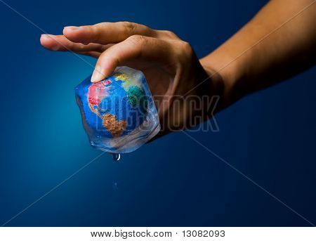 Conceptual image of global warming and green environmentalism. Human hand holding earth globe frozen into thawing ice cube.