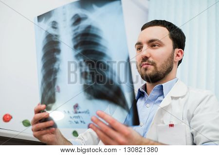 close up portrait of doctor looking at chest x ray in his office.