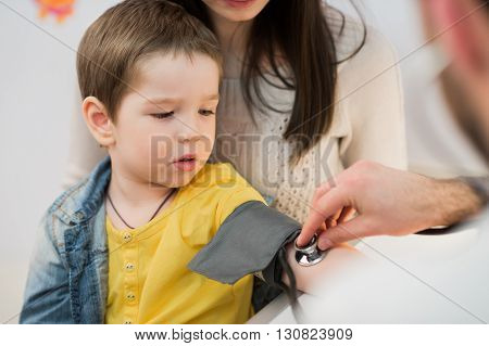 Little boy medical visit - doctor measuring blood pressure of a child.