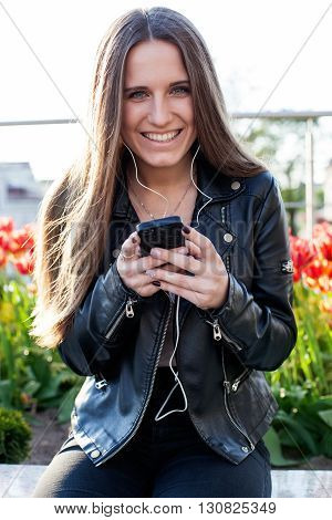 Young woman in black coat and jeans is sitting on the stone parapet holding a smartphone in the hands and listening to music in the headphones red flowers behind her