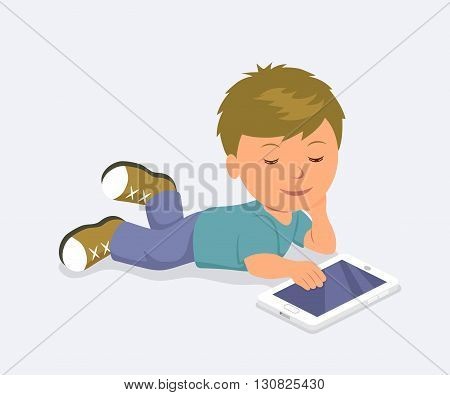 Baby lying down playing mobile games on the tablet. Learning, education and communication on the Internet using a mobile PC.