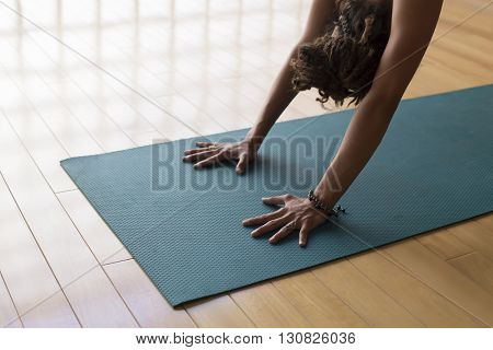 Closeup of woman hands in downward facing dog.