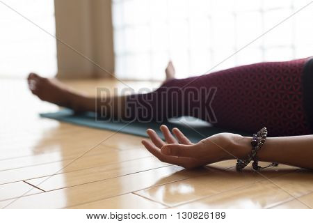 Beautiful woman lying down in her yoga mat during shavasana.