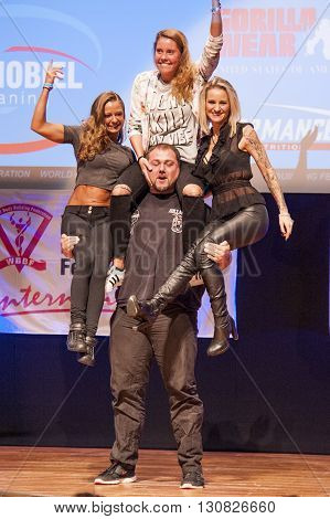 MAASTRICHT THE NETHERLANDS - OCTOBER 25 2015: Belgium strongman Jimmy Laureys lifts girls on stage at the World Grandprix Bodybuilding and Fitness of the WBBF-WFF