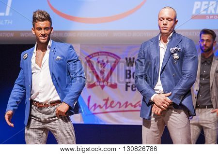 MAASTRICHT THE NETHERLANDS - OCTOBER 25 2015: Male fitness models dressed in suit show their best on stage at the World Grandprix Bodybuilding and Fitness of the WBBF-WFF