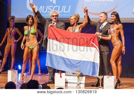 MAASTRICHT THE NETHERLANDS - OCTOBER 25 2015: Female figure models Larissa van Meerten and others celebrates their victory with the national flag of the Netherlands on stage at the World Grandprix Bodybuilding and Fitness of the WBBF-WFF