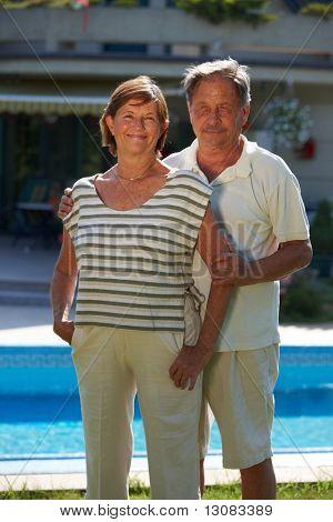 Retrato de la feliz pareja senior activo posando al aire libre frente a casa.