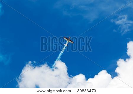 Red and white sport plane flies up releasing a stream of smoke into the blue sky with clouds