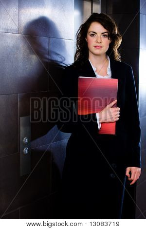 Young businesswoman holding red folder and posing for portrait on office corridor, looking at camera.