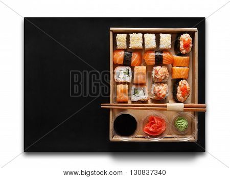 Japanese food restaurant, sushi maki gunkan roll plate or platter set. Chopsticks, ginger, soy sauce, wasabi. Sushi isolated at white background and black mat, take away, delivery box. Top view.