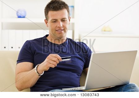 Man shopping online from home using credit card and laptop.