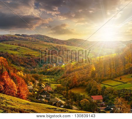 Village Falls On Hillside With Autumn Forest In Mountain At Sunset