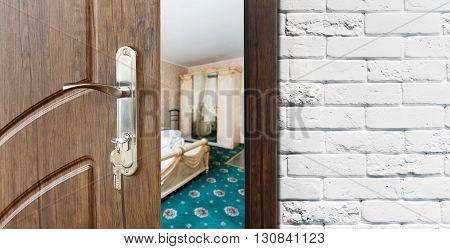 Half opened door to a bedroom. Door handle, door lock. Lounge door half open. Opening door. Welcome, privacy concept. Entrance to the room. Door at white brick wall, modern interior design.