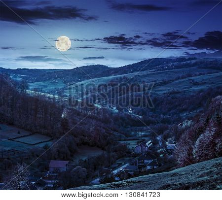 Village Falls On Hillside With Autumn Forest In Mountain At Night